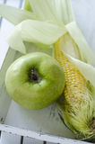 Year yield. Green apple and corn on the cob on a white wooden tray Stock Image