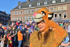 Yearly carnival in Nivelles, Belgium. NIVELLES, BELGIUM-MARCH 03, 2014: Unidentified happy participant of parade demonstrates her costume in defile during yearly stock images