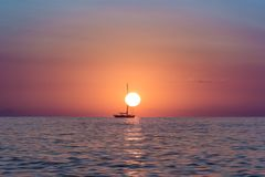 Sun rise in the ocean with a boat floating in front of the sun Stock Photos