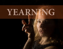 Yearning written on virtual screen. hand of young woman melancholy and sad at the window in the rain Royalty Free Stock Photo