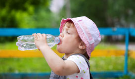 2 years baby drinks from  bottle. 2 years baby drinks from plastic bottle in park Stock Images