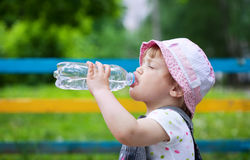 Baby drinks from plastic bottle. 2 years baby drinks from plastic bottle in park Royalty Free Stock Photography