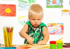 2 years boy drawing. 2 years old blond boy drawing with pencil on preschool art class with images on background Stock Images