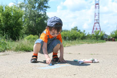 3 years boy draws with chalks in summertime outdoors Stock Image