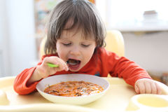2 years boy eating soup red-beet soup royalty free stock photography