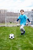7 years boy kicking ball in the garden. Stock Images