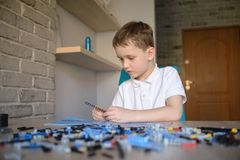 6 years boy playing with technic plastic blocks indoor. Active kid boy having fun with building and creating Royalty Free Stock Image