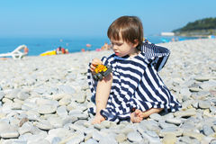 2 years boy in striped blanket sitting on the pebbles beach and Royalty Free Stock Image
