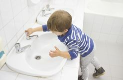 3 years boy washing hands at adapted school sink. Learning hygiene habits stock images