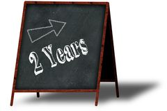 2 YEARS in chalk on wooden menu blackboard. Illustration concept Stock Images
