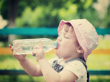 2 years child drinks from plastic bottle. In park Stock Photo