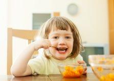 2 years  child eats carrot salad Stock Photo