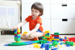 3 years child playing plastic blocks at home. Cute little boy (3 years) playing plastic blocks at home royalty free stock photos