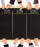 Years concept. Photo of business hands holding blackboard and writing timeline with 2013, 2014 and 2015 years stock images