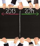 Years concept. Photo of business hands holding blackboard and writing timeline with 2013 and 2014 years stock illustration