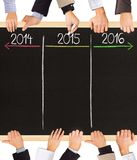 Years concept. Photo of business hands holding blackboard and writing timeline with 2014, 2015 and 2016 years stock illustration