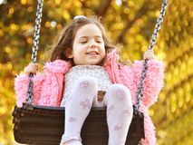3 years girl flying on swing. Little girl playing on swing. Portrait of my daughter playing with a beautiful expression. Big smille and happy face Stock Photos