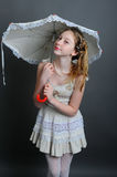 12-13 years girl under an umbrella. Smiling girl 12-13 years standing in studio under an umbrella on a dark background Royalty Free Stock Images