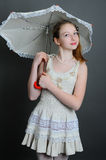 12-13 years girl under an umbrella. Smiling girl 12-13 years standing in studio under an umbrella on a dark background Stock Images