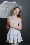12-13 years girl under an umbrella. Smiling girl 12-13 years standing in studio under an umbrella on a dark background Royalty Free Stock Photos