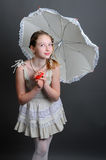 12-13 years girl under an umbrella. Smiling girl 12-13 years standing in studio under an umbrella on a dark background Royalty Free Stock Photo