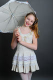 12-13 years girl under an umbrella. Smiling girl 12-13 years standing in studio under an umbrella on a dark background Stock Photography