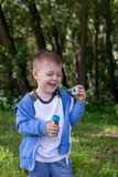 Active kid playing in the garden on a sunny summer day, Out doors activities for children. 4 years Little boy with soap bubbles in summer green trees park, funny royalty free stock photos