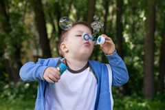 Active kid playing in the garden on a sunny summer day, Out doors activities for children. 4 years Little boy with soap bubbles in summer green trees park, funny stock photography
