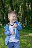 4 years Little boy with soap bubbles in summer green trees park, funny leisure time. Boy in the park blowing soap bubbles. And having fun Royalty Free Stock Photo