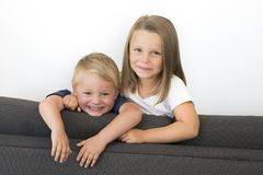 7 years old beautiful little girl posing happy at home sofa couch with her small cute young 3 years old brother in siblings love r Royalty Free Stock Photo