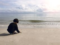 4 years old Asian boy sand writing  on beach with sea and sky ba. 4 years old black hair Asian boy sand writing lonely on beach with sea and sky background with Royalty Free Stock Photo