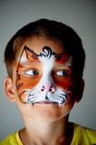 Years old boy with blue eyes  face painting of a cat or  tiger. Orange. 6 years old boy with blue eyes with face painting of a cat or a tiger. Orange Stock Images