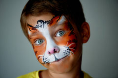 Years old boy with blue eyes  face painting of a cat or  tiger. Orange. Royalty Free Stock Image