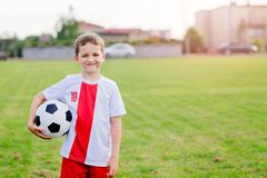 8 years old boy child holding football ball. On playing field. Child playing football Stock Image