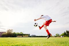 8 years old boy child kicking ball on playing field. royalty free stock image