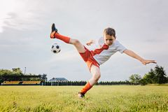 8 years old boy child playing football and rolls over. After foul. Child playing football royalty free stock image