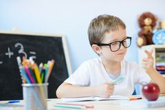 7 years old boy counting on fingers. 7 years old boy solves multiplication table in his copybook and counting on fingers. Back to school Royalty Free Stock Photos