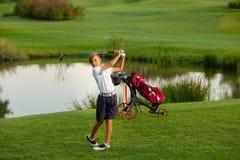 11 years old boy golfer playing golf near a lake stock photo
