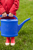 4 years old boy in a red jacket and rubber boots is going to water a tree and from a nice big blue watering can. Stock Photo