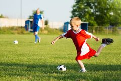 Soccer training for children. The 4 years old boy is shooting the soccer ball on soccer sport training outdoors on playing field stock photo