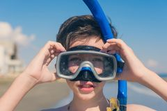 13 years old boy in the snorkeling mask and tube for diving in the sea wave. Travel and summer concept. stock photos