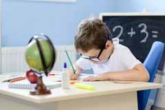 7 years old boy solves multiplication table in his copybook. Stock Image