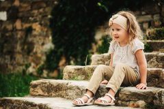 5 years old child girl sitting on old stone stairs Royalty Free Stock Image