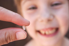 At 6 years old child has lost the baby tooth. The girl is holding the tooth in his hand.  stock photography