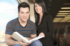 A 20 years old couple student studying. A 20 years old couple student with a book on the side of a window Stock Image