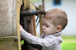 2 years old curious Baby boy managing with old agr. Icultural Machinery Royalty Free Stock Images