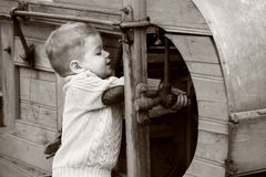 2 years old curious Baby boy managing with old agr. Icultural Machinery on sepia brown color Royalty Free Stock Photography