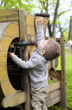 2 years old curious Baby boy managing with old agricultural Mach Stock Images