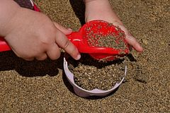 3 years old girl hands putting sand into pink pattypan form with red shovel Royalty Free Stock Images