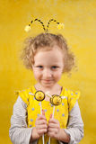 Girl with bee cake pops. 3 years old girl is holding bee cake pops against yellow background stock photos